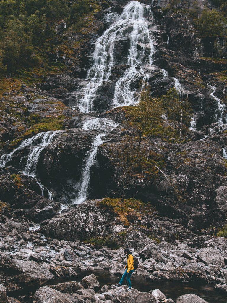 dame met gele jas loopt langs waterval